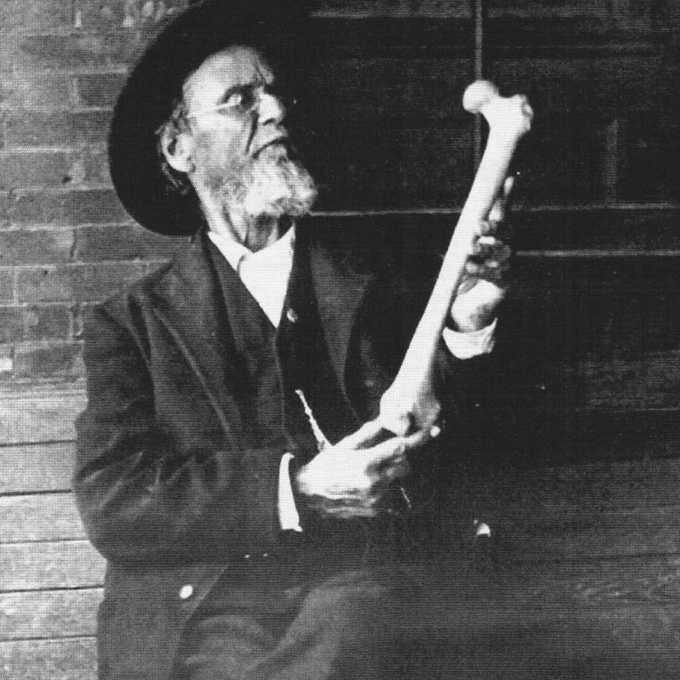 Fondateur ostéopathie avec un fémur dans la main