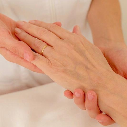mains de l'ostéopathe à Paris et celle de sa patiente atteinte de la maladie de parkinson